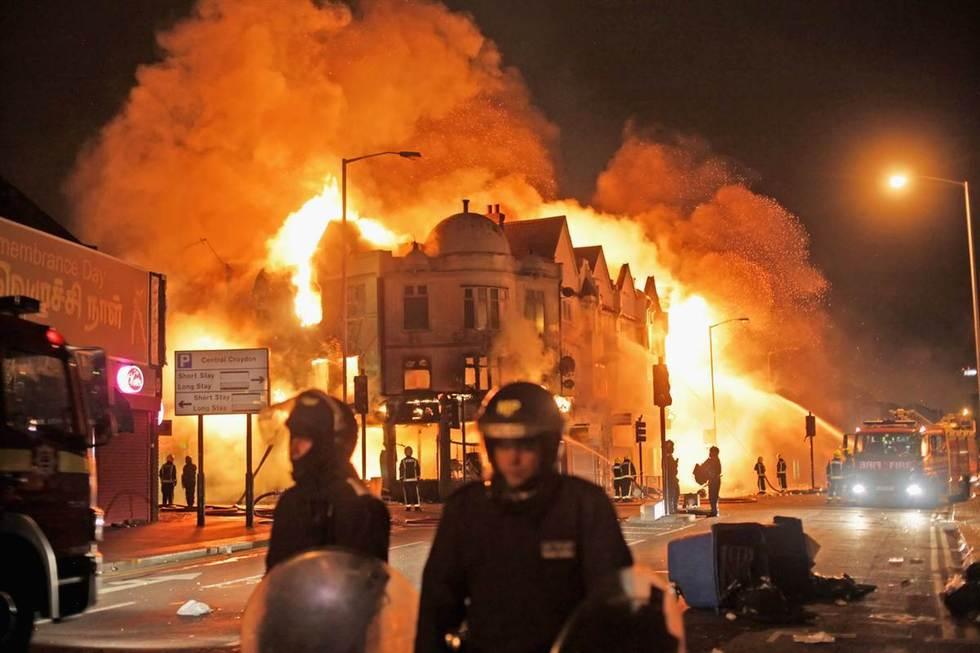8月9日,伦敦南部克罗伊登,消防员扑救被点燃的民房。
