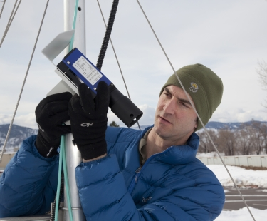 Ethan Gutmann examines a laser instrument for measuring snow.